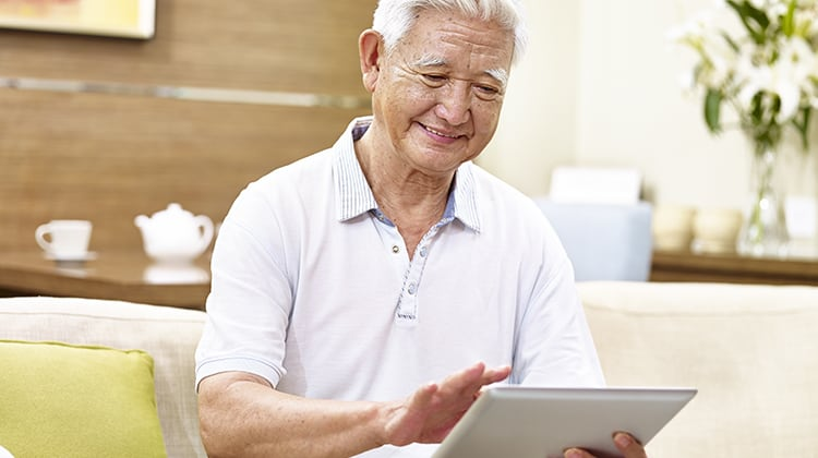active senior asian man sitting on couch using tablet computer, relaxed, smiling